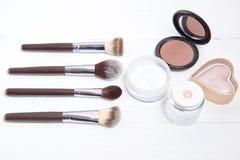 Herramientas profesionales del maquillaje en el fondo de madera blanco Imagenes de archivo