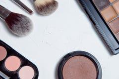 Herramientas profesionales del maquillaje en el fondo de madera blanco Foto de archivo libre de regalías