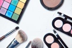 Herramientas profesionales del maquillaje en el fondo de madera blanco Foto de archivo