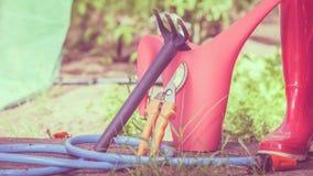 Herramientas que cultivan un huerto al aire libre en jardín Imagen de archivo