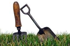 Herramientas que cultivan un huerto antiguas en hierba Foto de archivo