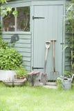 Herramientas que cultivan un huerto contra la puerta de la vertiente Fotografía de archivo libre de regalías