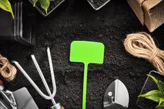 Herramientas que cultivan un huerto y plantas imagen de archivo