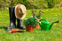 Herramientas que cultivan un huerto y un sombrero de paja Imagenes de archivo