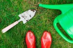 Herramientas que cultivan un huerto, zapatos rojos del jardín, pequeña espada, regadera en la hierba, cierre para arriba imagen de archivo