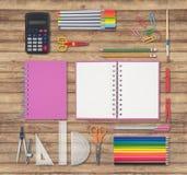 Herramientas rosadas del cuaderno y de la escuela o de la oficina en el fondo de madera Imagen de archivo