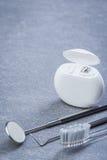 Herramientas, seda y cepillo dentales básicos en superficie gris Imágenes de archivo libres de regalías