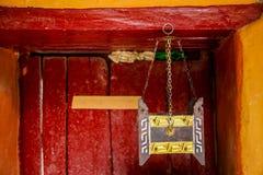 Herramientas tibetanas antiguas del incienso en templo budista contra puerta de madera roja Imagenes de archivo