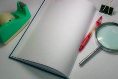 Herramientas todavía de la vida del cuaderno y de los efectos de escritorio en fondo ligero oscuro Imagen de archivo