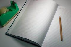 Herramientas todavía de la vida del cuaderno y de los efectos de escritorio en fondo ligero oscuro Fotos de archivo libres de regalías