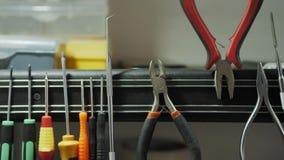 Herramientas a utilizar en instalaciones eléctricas Multímetro de Digitaces en fondo Destornillador de la toma de la mano metrajes
