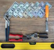 Herramientas viejas de la construcción y un sistema de billetes de dólar en un primer de madera de la tabla imagen de archivo