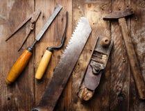 Herramientas viejas de la mano del vintage en fondo de madera Foto de archivo