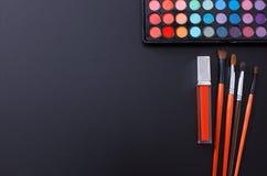 Herramientas y accesorios del maquillaje aislados en fondo negro Visión superior y mofa para arriba El lápiz labial, sombras de o Fotos de archivo libres de regalías
