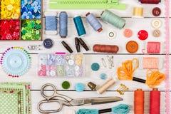 Herramientas y accesorios para coser en fondo de madera ligero Foto de archivo libre de regalías
