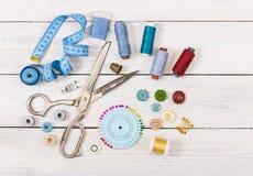 Herramientas y accesorios para coser en fondo de madera ligero Fotografía de archivo