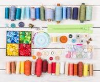Herramientas y accesorios para coser en fondo de madera ligero Imagen de archivo libre de regalías