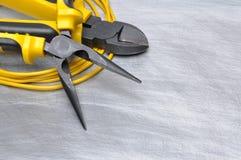 Herramientas y cables eléctricos en superficie de metal con el lugar para el texto Imagenes de archivo