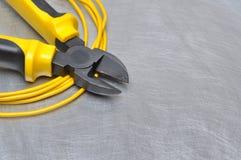 Herramientas y cables eléctricos en superficie de metal con el lugar para el texto Fotos de archivo libres de regalías