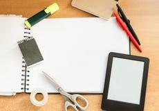 Herramientas y ebook de la oficina en una tabla de madera Fotografía de archivo libre de regalías
