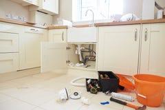 Herramientas y equipo de Plumber's en un piso de la cocina imágenes de archivo libres de regalías