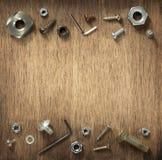 Herramientas y tornillos del hardware en la madera imagen de archivo