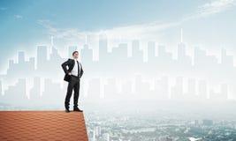 Herrchef auf Ziegelsteindach mit den Armen in die Seite gestemmt Gemischte Medien Stockfoto