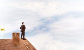 Herrchef auf Ziegelsteindach mit den Armen in die Seite gestemmt Gemischte Medien Lizenzfreies Stockfoto