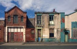 Herrelöst godshus och övergett garage på en bostads- gata arkivfoto