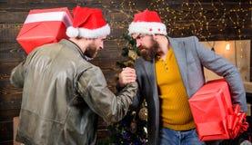 Herrenbekleidungssankt-Hutgriffgeschenkboxen Bärtige Männer tragen Präsentkartons Grobe Hippie-Kerle feiern Weihnachten mit Gesch lizenzfreies stockbild