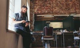 Herrenfriseur, der digitale Tablette an seinem Shop verwendet lizenzfreie stockfotografie