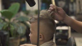 Herrenfriseur, der Jungenfrisur mit Trockner im Friseursalon tut Kinderhaartrockner im Frisörsalon friseur stock footage
