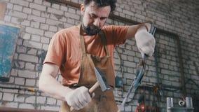 Herrero con el martillo en la fragua que crea el cuchillo de acero Fotografía de archivo