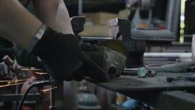 Herrero de la mujer que corta un pedazo de metal usando una máquina de pulir que hace chispas en contacto con el tornillo del hie almacen de metraje de vídeo