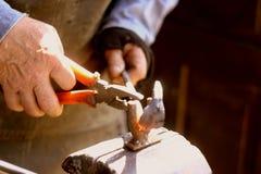 Herrero de las manos con una herramienta foto de archivo