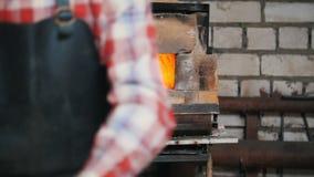 Herrero en el trabajo Haciendo el fuego en pequeño horno, después de que el trabajador ponga los objetos en horno metrajes