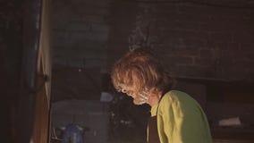 Herrero en los trabajos de la fragua al lado del horno Calor intenso Su figura es encendida por las llamas de la estufa Tiro agra almacen de video