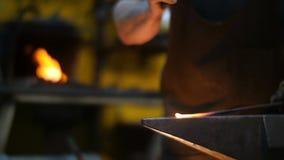 Herrero Hitting Hot Metal con un martillo en un yunque dentro de su taller almacen de video