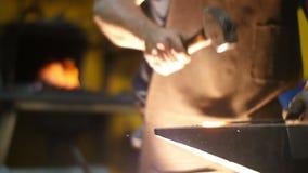 Herrero Hitting Hot Metal con un martillo en un yunque dentro de su taller en la cámara lenta almacen de metraje de vídeo