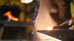 Herrero Hitting Hot Metal con un martillo en un yunque dentro de su taller en la cámara lenta almacen de video