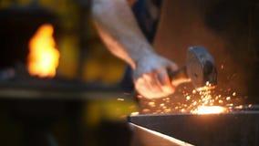Herrero Hitting Metal con un martillo en un yunque dentro de su taller almacen de video