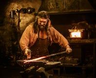 Herrero mayor que forja el metal fundido en el yunque en herrería Imagen de archivo