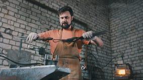 Herrero muscular en la fragua que martilla los productos de acero Fotografía de archivo