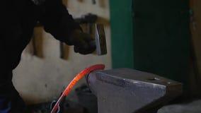 Herrero que martilla el extremo de barras de hierro en un gancho almacen de video