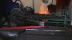 Herrero que martilla el extremo de barras de hierro en un gancho fotos de archivo