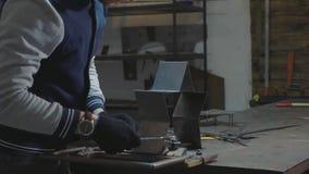 Herrero que trabaja con el detalle decorativo del metal en su taller almacen de metraje de vídeo
