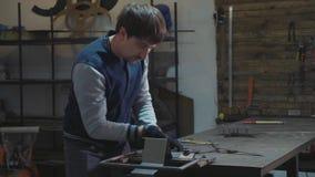 Herrero que trabaja con el detalle decorativo del metal en su taller almacen de video