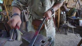 Herrero que trabaja con una pieza de metal en stithy en fragua almacen de metraje de vídeo
