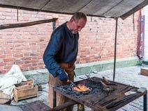 Herrero que trabaja en el mercado medieval de los artes imágenes de archivo libres de regalías