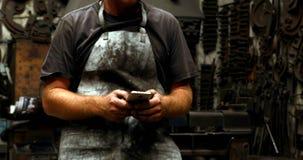 Herrero que usa el teléfono móvil en el taller 4k